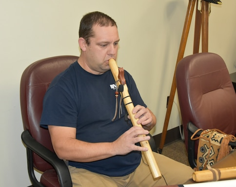 Kevin Ashley, an inside machinist with the Arnold Engineering Development Complex Model and Machine Shop at Arnold Air Force Base, Tenn., plays one of the Native American flutes he made. Ashley began playing the Native American flute around 20 years ago after purchasing his first and has been making his own flutes for more than a decade. (U.S. Air Force photo by Bradley Hicks) (This image has been altered by obscuring badges for security purposes.)