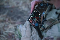 A Soldier from the 2-506, 101st Airborne Division checks his Nett Warrior end user device (EUD) during a full mission test event at a Soldier Touchpoint at Aberdeen Proving Ground, MD in February 2021.