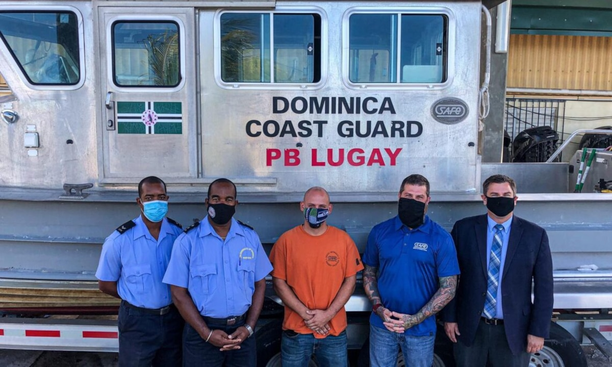U.S. and Dominican personnel stand in front of a Dominica Marine Unit vessel.