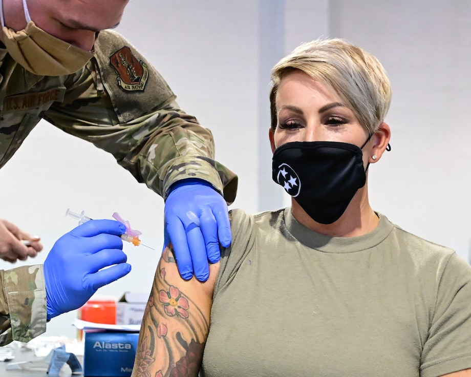 Master Sgt. Amy Robinson receives the first dose of the COVID-19 vaccine.
