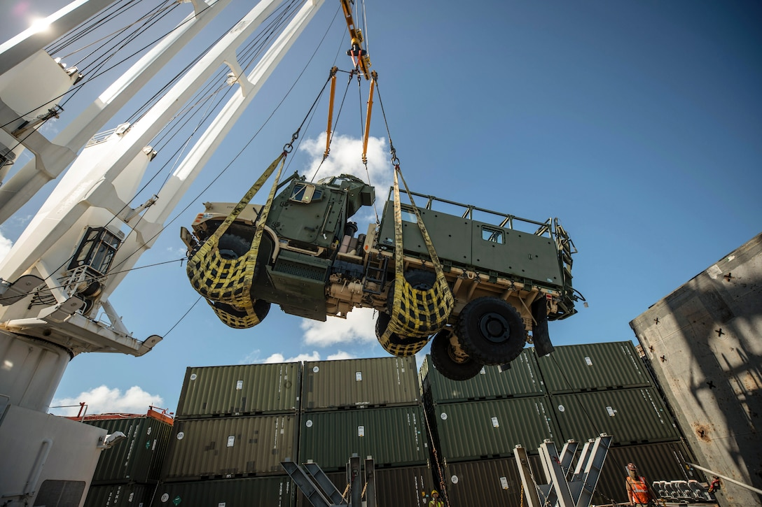 Marines and sailors lift a vehicle on a ship.