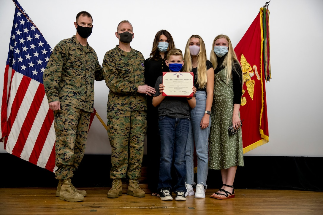 U.S. Marine Corps Brig. Gen. Kyle Ellison, Commanding General for 3rd Marine Expeditionary Brigade, poses for a photo with Capt. Kevin. W. Leishman, an Anti-Terrorism force protection officer, 3D MEB, and his family after a Purple Heart ceremony at the base theater, Camp Courtney, Okinawa, Japan, Feb. 24, 2021. During the ceremony Leishman was awarded for wounds sustained in action against enemies of the United States 16 years ago during the Battle of Fallujah, Operation Phantom Fury, Operation Iraqi Freedom. (U.S. Marine Corps photo by Cpl. Francesca Landis)