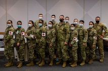 Col. Stephen R. Jones, 432nd Wing/432nd Air Expeditionary Wing commander, stands shoulder to shoulder with 99th Medical Group medical staff at Nellis Air Force Base.