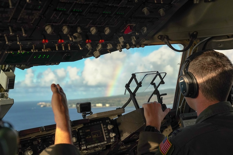 Col. Scott Berndt, 15th Wing Operations Group commander, points out a rainbow to Capt. Garrison Boone, 535th Airlift Squadron pilot, during a flight training exercise around the Hawaiian Islands, Jan. 31, 2021. The C-17 Globemaster III can perform many different flight maneuvers including tactical airlift and airdrop missions. (Air Force photo by Airman 1st Class Makensie Cooper)