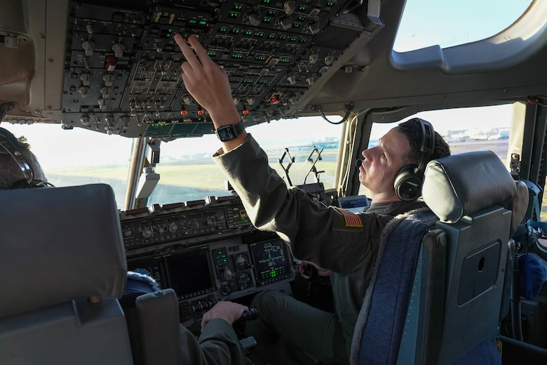 Capt. Garrison Boone, 535th Airlift Squadron pilot, adjusts controls in the cockpit to prepare for the final approach to land at Joint Base Pearl Harbor-Hickam, Hawaii, Jan. 31, 2021. The 535th AS conducted a go-around mission over Maui, a training exercise where the landing is aborted during the final approach.  (Air Force photo by Airman 1st Class Makensie Cooper)