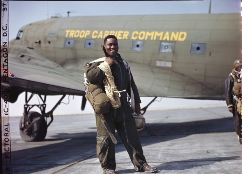 Army Lt. Clifford Allen of Chicago, Illinois, is one of the fire fighters of the all-black 555th Parachute Infantry Battalion. He wears his complete outfit just before taking off for a jump. Note the 150 ft. rope descending from tall trees; the plastic helmet and catcher's mask are protections against branches and brambles. Known as the Triple Nickles, the 555th completed 1200 jumps from July-October 1945 in support of the U.S. Forest Service efforts to contain forest fires in the northwest United States. The smokejumpers parachuted into regions difficult for firefighters to reach and helped contain 36 fires during this time.