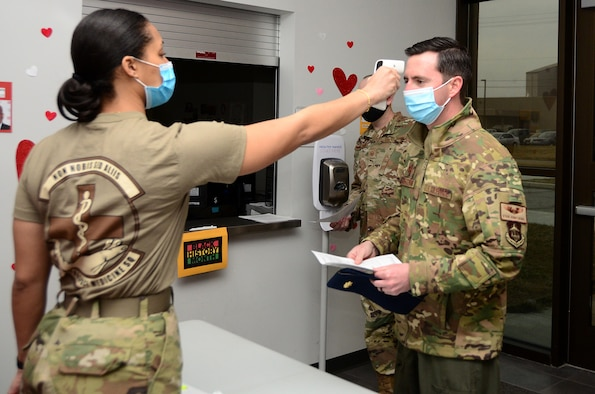 Senior Airman Mariah Harris, 44th Aerospace Medicine Squadron commanders support staff, takes the temperature of Maj. Ryan Armstrong, 89th Airlift Squadron C-17 pilot, before he signs in to get his Moderna COVID-19 vaccine Feb. 26, 2021, Wright Patterson Air Force Base, Ohio. To prevent the spread of COVID-19, Airmen were given staggered time slots and maintained physical distancing per Centers for Disease, Control and Prevention guidelines. (U.S. Air Force photo/Mr. Darrell Sydnor)