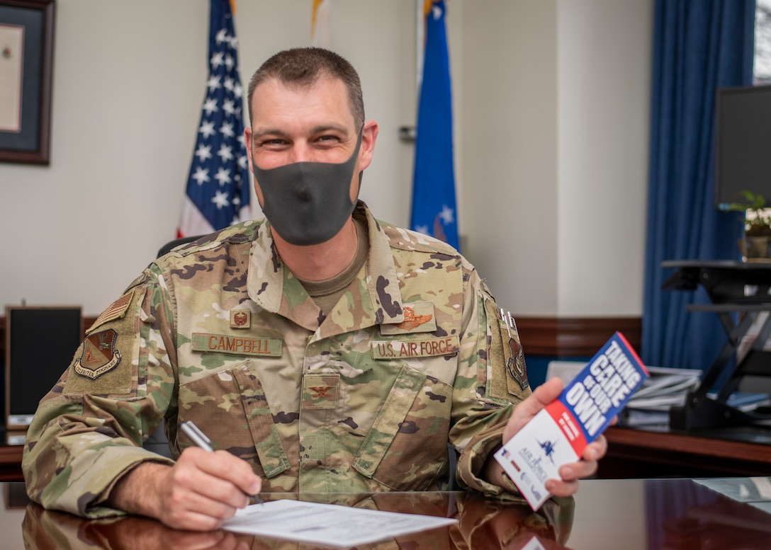 Col. Andrew Campbell sits at a desk, signing a donation