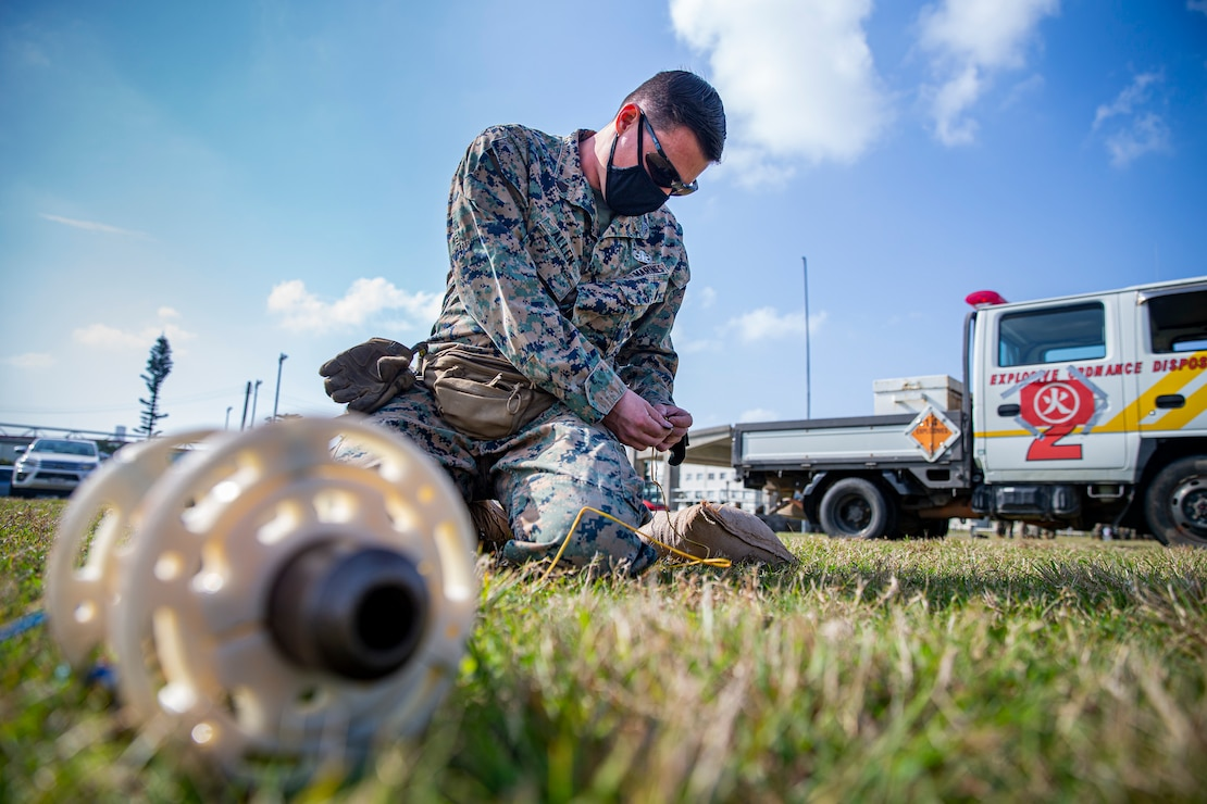 U.S. Marine Corps Sgt. Timothy Allen, an explosive ordnance disposal (EOD) technician with Marine Corps Base Camp Butler EOD, creates a circuit using firing wire on Camp Hansen, Okinawa, Japan, Feb. 25, 2021. EOD technicians and artillery Marines conducted normal M777 Howitzer firing procedures, however, dummy rounds were intentionally lodged in the 16.7 ft. barrel of the weapon system so each unit could demonstrate their extraction techniques. Allen is a native of Warsaw, Missouri. (U.S. Marine Corps photo by Lance Cpl. Alex Fairchild)