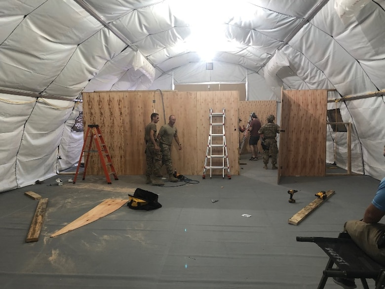 Airmen with the 435th Air Ground Operations Wing and the 435th Air Expeditionary Wing work together to construct a field resuscitative surgical tent at a base in East Africa, Dec. 15, 2020. Airmen of the 435th AGOW and 435th AEW took part in the movement of personnel and cargo to support Operation Octave Quartz. (Courtesy photo)