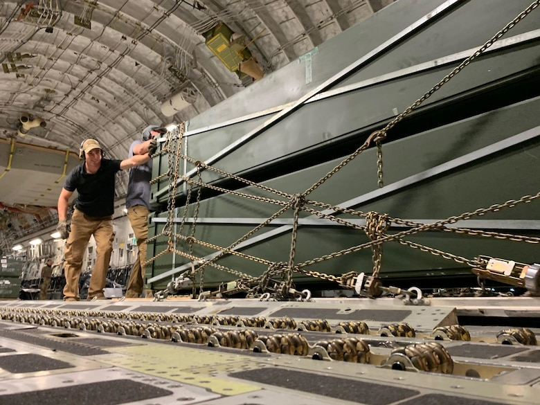 U.S. Air Force Airmen assigned to the 435th Air Expeditionary Wing push cargo off a U.S Air Force C-130J Super Hercules aircraft during Operation Octave Quartz