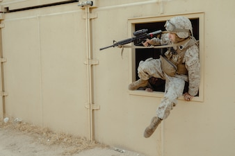 Hospital Corpsman 2nd Class Zachary Knueven maneuvers through a window during Integrated Training Exercise (ITX) 2-21 on Marine Corps Air Ground Combat Center Twentynine Palms, California.