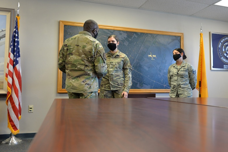 Command Chief Master Sgt. Maurice Williams gives a coin to Senior Airman Shelby Snow as her supervisor watches in a conference room setting with an American flag to the left and the New Mexico state flag to the right