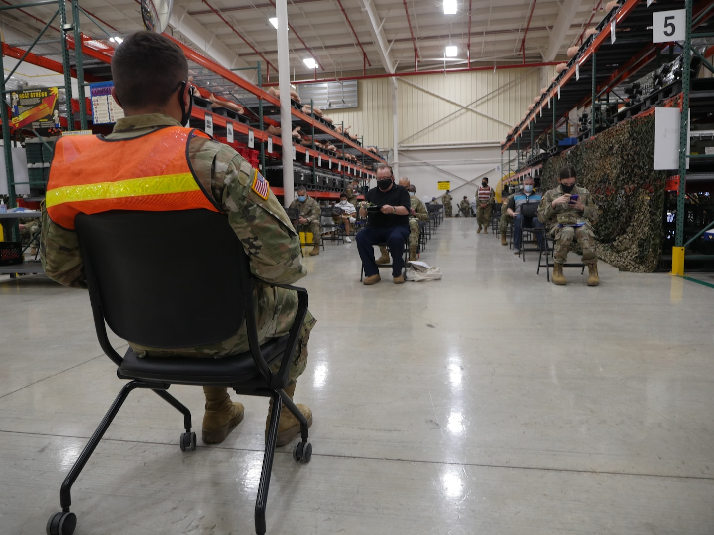 Military and civilian personnel wait the required 15-30 minutes after receiving their COVID-19 vaccination shot.
