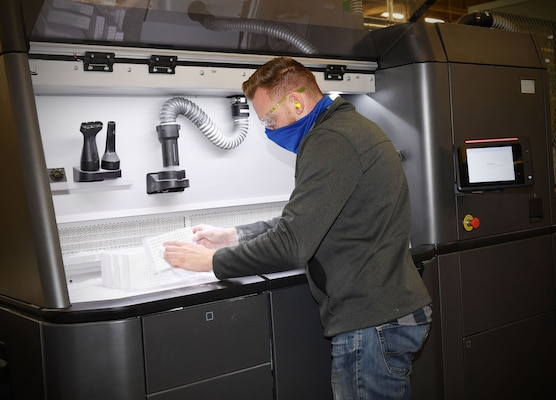 Fleet Readiness Center Southeast (FRCSE) mechanical engineer, Matthew Simon, removes excess nylon powder from 3D printed nasopharyngeal swab cages before going into an automated glass bead blaster for further processing.
