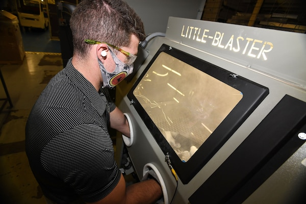 Fleet Readiness Center Southeast (FRCSE) mechanical engineer, Evan Grambling, utilizes a manual glass bead blaster as part of the processing procedures involved in the 3D printing of nasopharyngeal swabs.