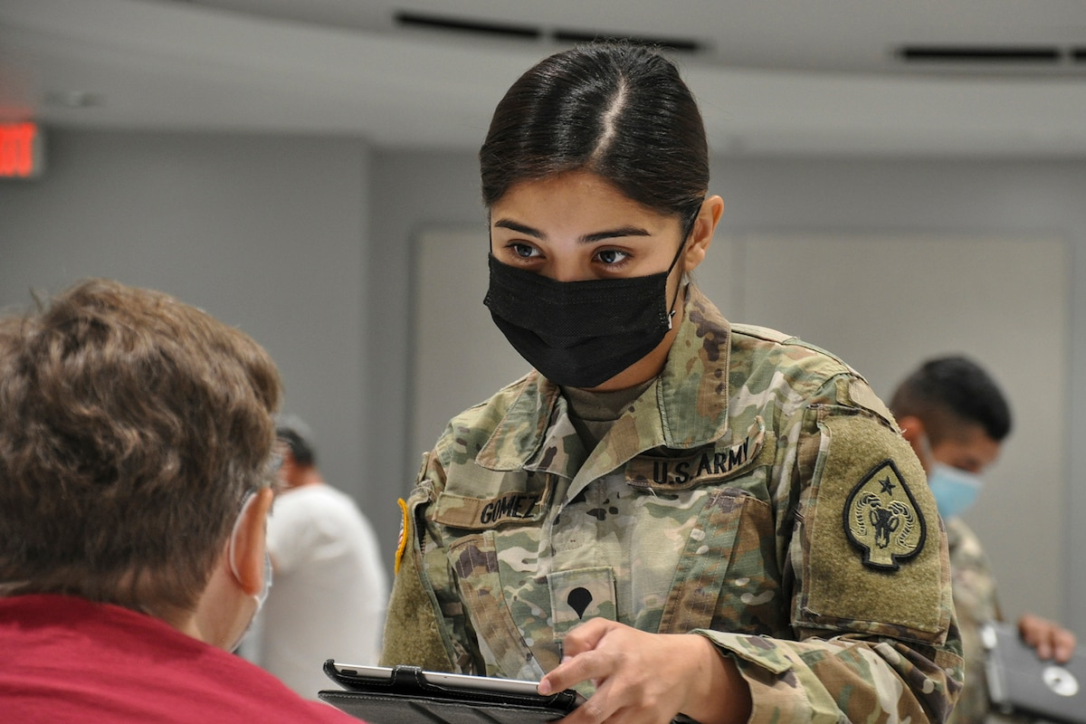 A soldier wearing a mask speaks to a civilian.