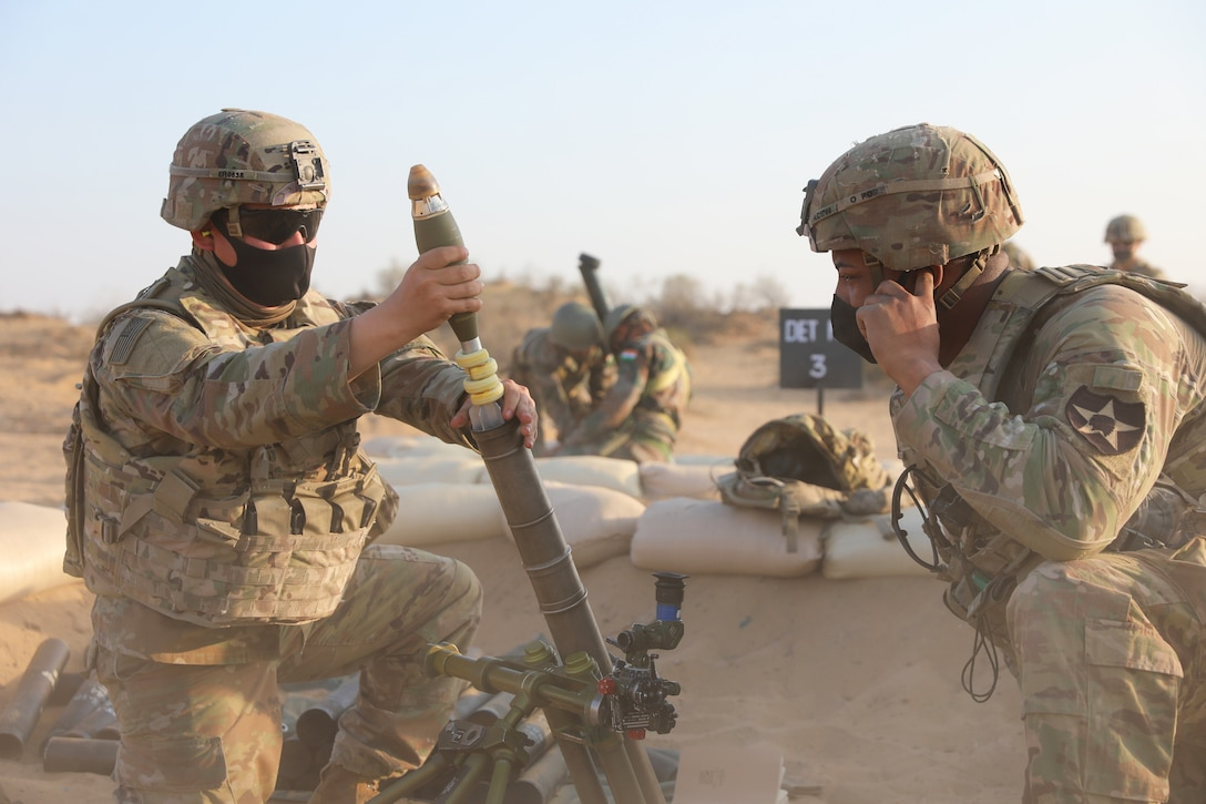 Two soldiers load a mortar firing while others do the same in the distance.