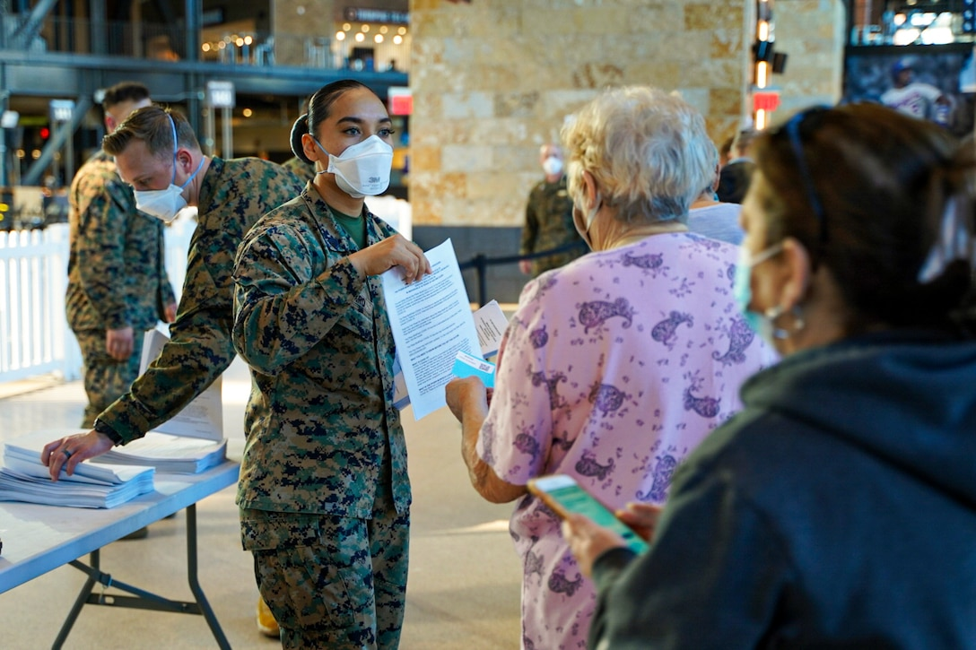 A Marine holds up a sheet of paper for a senior citizen standing in line.