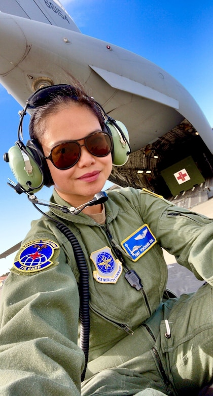 An Air Force Reserve medical professional takes photo near aircraft carrying medical equipment.