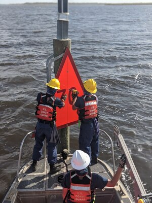 A crew form U.S. Coast Guard Aids to Navigation Team Sabine, Texas hangs new a dayboard on Lake Charles, Louisiana, Aug 31, 2020. The crew has been working to repair aids to navigation in the tributaries of the Gulf of Mexico in the wake of Hurricane Laura. (U.S. Coast Guard photo by Petty Officer 2nd Class Ronald Hodges)