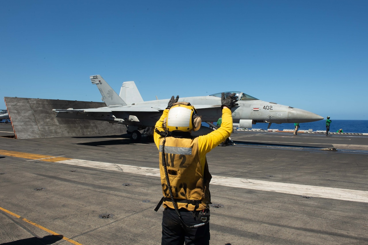 A service member directs a jet taking off from an aircraft carrier.