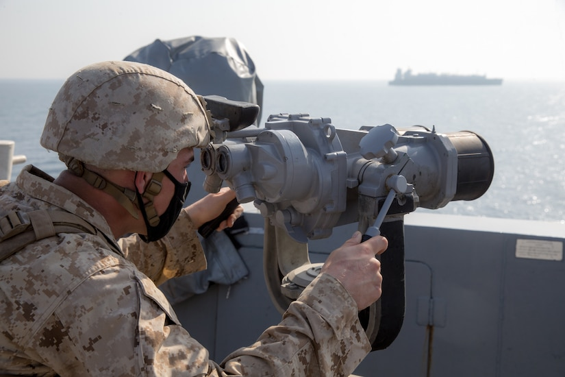 A male service member looks through a ship's bridge binoculars to scan the sea as a ship sails in the distance.