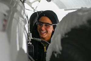Senior Airman Kendra Ancell, hydraulics technician with the 911th Aircraft Maintenance Squadron, shares a laugh during routine maintenance on a C-17 Globemaster III landing gear strut at the Pittsburgh International Airport Air Reserve Station, Pennsylvania, Feb. 1, 2021.