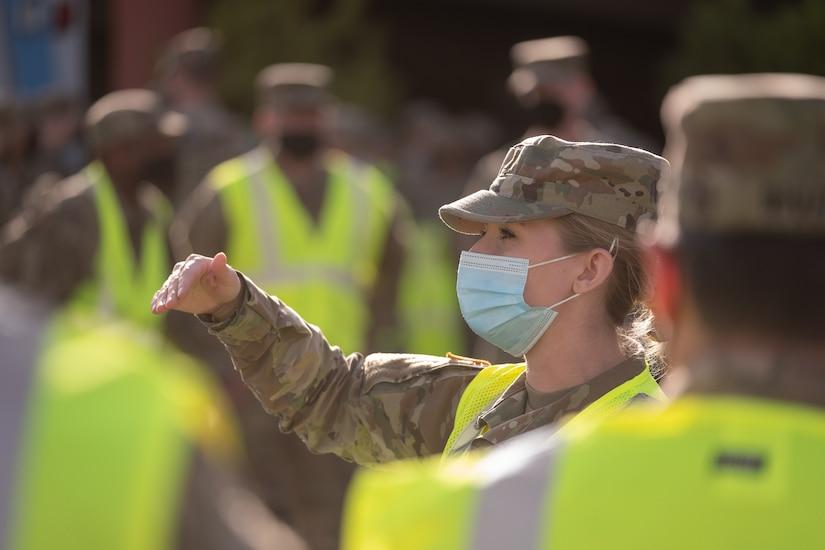 A nurse speaks to soldiers.