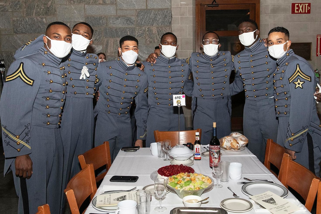 Cadets stand around a table.