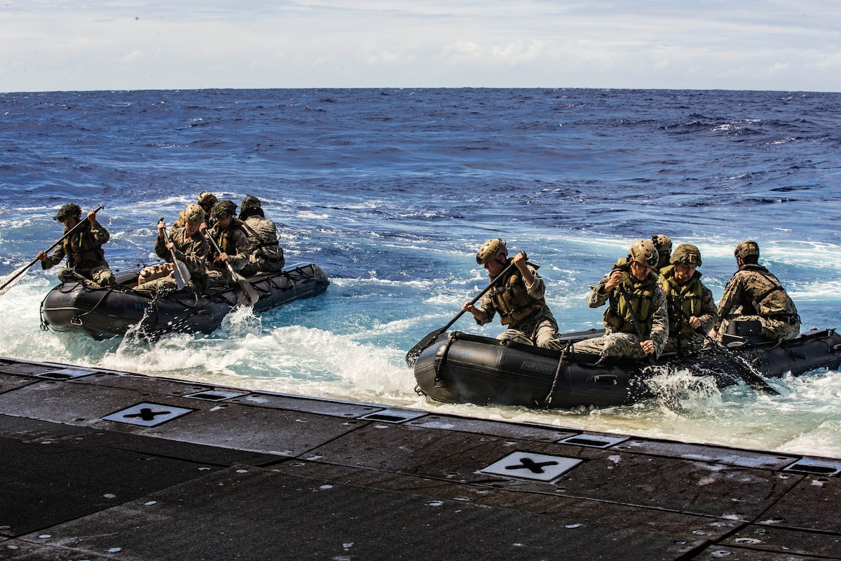 Marines offload in combat rubber raiding crafts from a ship at sea.