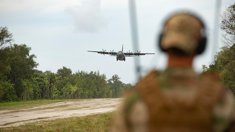 U.S. Air Force Capt. Gene Walker, 36th Contingency Response Squadron assistant director of operations, watches a C-130J Super Hercules from Yokota Air Base approach the landing zone during Cope North 21, Feb. 11, 2021, on Angaur, Palau.