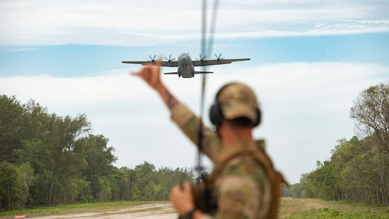 U.S. Air Force Capt. Gene Walker, 36th Contingency Response Squadron assistant director of operations, waves on a C-130J Super Hercules from Yokota Air Base as it approaches the landing zone during Cope North 21, Feb. 11, 2021, on Angaur, Palau.