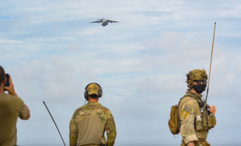 Members of the 36th Contingency Response Group watch as a Koku-Jieitai Kawasaki C-2, assigned to the 403rd Squadron from Miho Air Base, approaches for an airdrop during Cope North 21, Feb. 10, 2021, on Angaur, Palau.