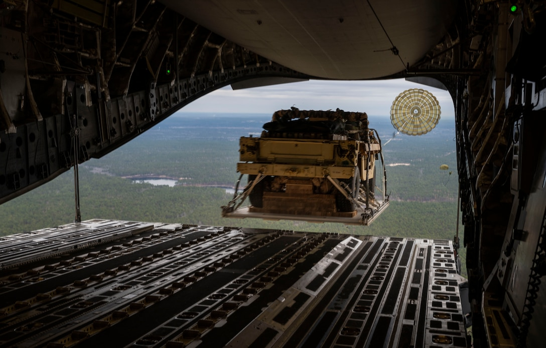 A Humvee is airdropped from a C-17 Globemaster III, assigned to the 62nd Airlift Wing, Joint Base Lewis-McChord, Wash., during Exercise Predictable Iron at Pope Army Airfield, Fort Bragg, N.C., Feb. 26, 2021. Members with the 62nd AW conducted airdrop and personnel drop missions with the 82nd Airborne Division, promoting the integration of mobility capabilities into joint warfighting concepts.