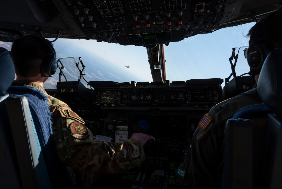 Capt. Tim Wilson, left, 8th Airlift Squadron pilot, and Capt. Evan Maes, 8th AS copilot, fly a C-17 Globemaster III assigned to the 62nd Airlift Wing, Joint Base Lewis-McChord, Wash., in a formation flight during Exercise Predictable Iron at Pope Army Airfield, Fort Bragg, N.C., Feb. 25, 2021. The exercise provided the opportunity for the U.S. Air Force and U.S. Army to strengthen their skill sets together and accomplish the Department of Defense's mission to provide combat-credible military forces.
