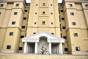 An Airman cycles by a building.