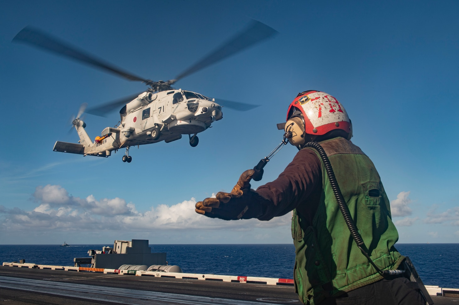 PACIFIC OCEAN (Feb 28, 2021) – U.S. Navy Airman Alexis Neff, from Jacksonville, Fla., directs the pilot of a Japan Maritime Self-Defense Force (JMSDF) MH-60 Sea Hawk to land on the flight deck of the aircraft carrier USS Theodore Roosevelt (CVN 71) Feb. 28, 2021. The Theodore Roosevelt Carrier Strike Group is on a scheduled deployment to the U.S. 7th Fleet area of operations. As the U.S. Navy's largest forward-deployed fleet, 7th Fleet routinely operates and interacts with 35 maritime nations while conducting missions to preserve and protect a free and open Indo-Pacific Region. (U.S. Navy photo by Mass Communication Specialist 3rd Class Erik Melgar)
