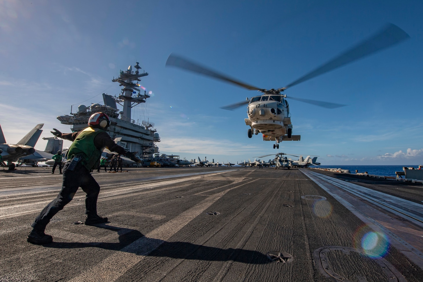 PACIFIC OCEAN (Feb 28, 2021) – U.S. Navy Airman Alexis Neff, from Jacksonville, Fla., directs the pilot of a Japan Maritime Self-Defense Force (JMSDF) MH-60 Sea Hawk to take off from the flight deck of the aircraft carrier USS Theodore Roosevelt (CVN 71) Feb. 28, 2021. The Theodore Roosevelt Carrier Strike Group is on a scheduled deployment to the U.S. 7th Fleet area of operations. As the U.S. Navy's largest forward-deployed fleet, 7th Fleet routinely operates and interacts with 35 maritime nations while conducting missions to preserve and protect a free and open Indo-Pacific Region. (U.S. Navy photo by Mass Communication Specialist 3rd Class Erik Melgar)