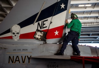 Sailors maintain aircraft aboard the Nimitz-class aircraft carrier USS Carl Vinson (CVN 70).