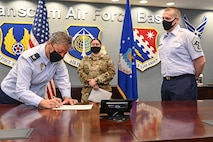 Col. Katrina Stephens, left, installation commander, signs a Women's History Month proclamation at Hanscom Air Force Base, Mass., March 2, while Chief Master Sgt. William Hebb, installation command chief, and Tech. Sgt. Christine Tuato'o, WHM project officer, look on. The observance recognizes women's contributions in America. This year's theme is 'Honoring the Past, Securing the Future!.' (U.S. Air Force photo by Todd Maki)