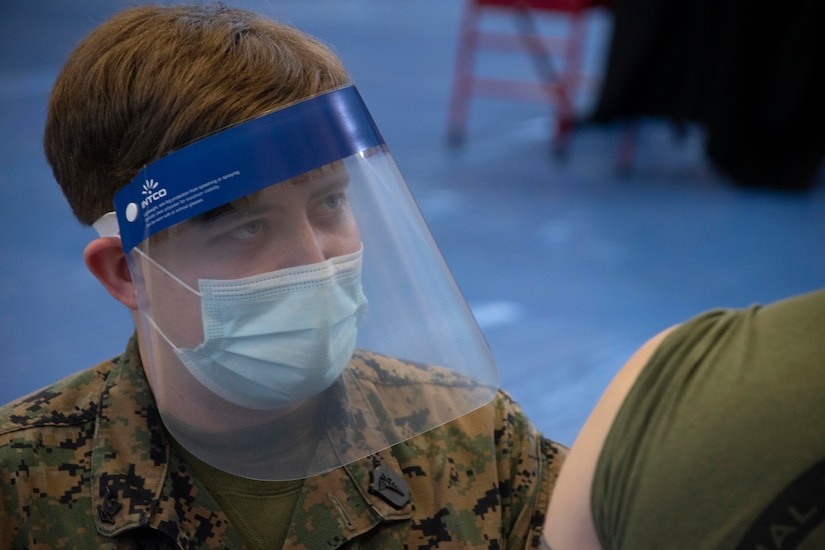 A sailor wearing a face mask and shield prepares to vaccinate a Marine.