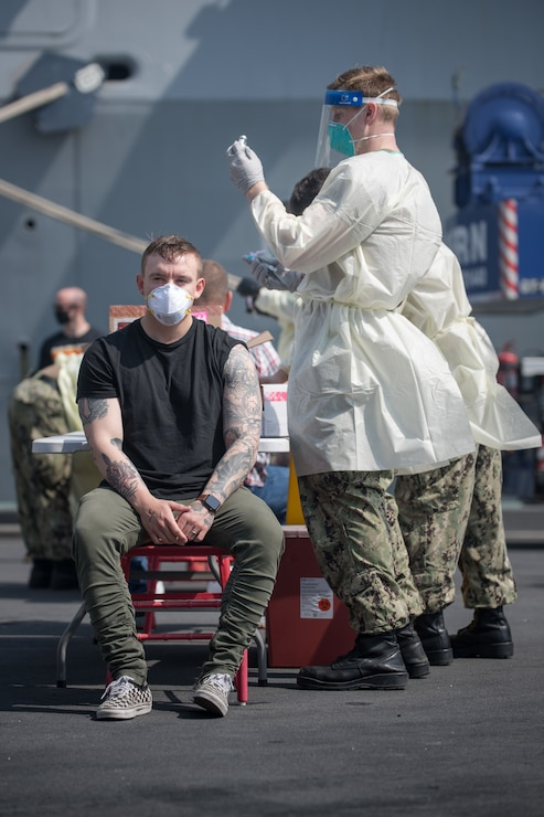 A hospital corpsman prepares to administer a COVID-19 vaccine to a Sailor assigned to the guided-missile cruiser USS Philippine Sea (CG 58) in Manama, Bahrain.