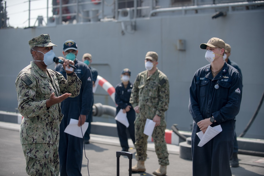 Chief Hospital Corpsman Darnell Mason, left, assigned to U.S. Naval Forces Central Command, delivers a COVID-19 vaccine brief to Sailors in Manama, Bahrain.