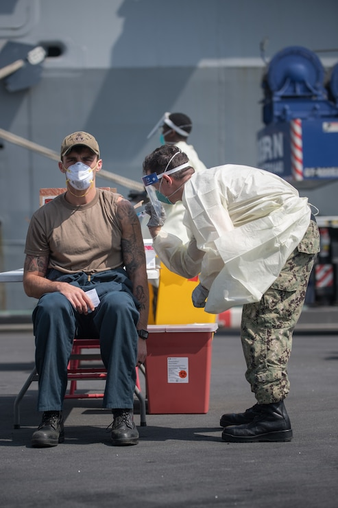 A hospital corpsman administers a COVID-19 vaccine to a Sailor assigned to the guided-missile cruiser USS Philippine Sea (CG 58) in Manama, Bahrain.