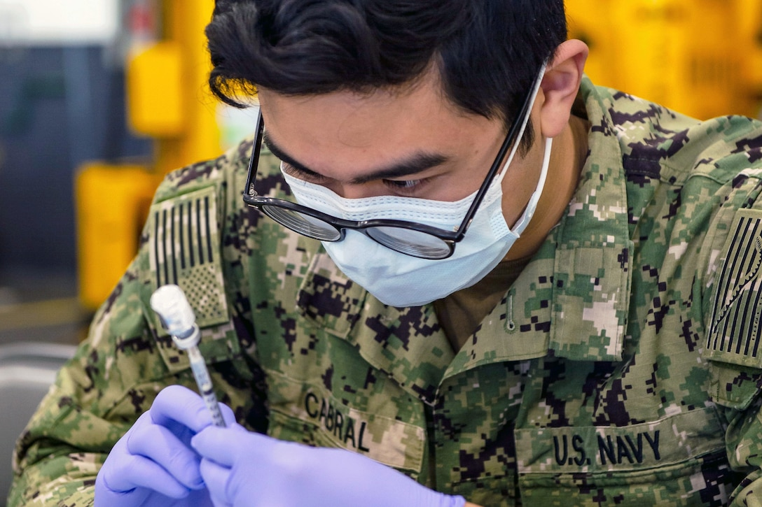 A service member wearing a face mask and gloves holds a syringe into a small bottle.