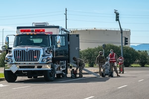 Airmen in bright vests unload a bomb-defusing robot from a truck