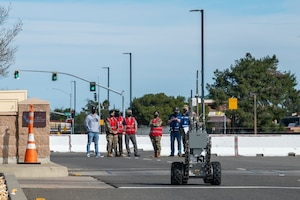 Airmen in bright vests look on at a bomb disposal robot