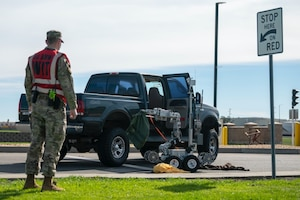 An Airman in a bright vest looks on at a parked truck with the door open