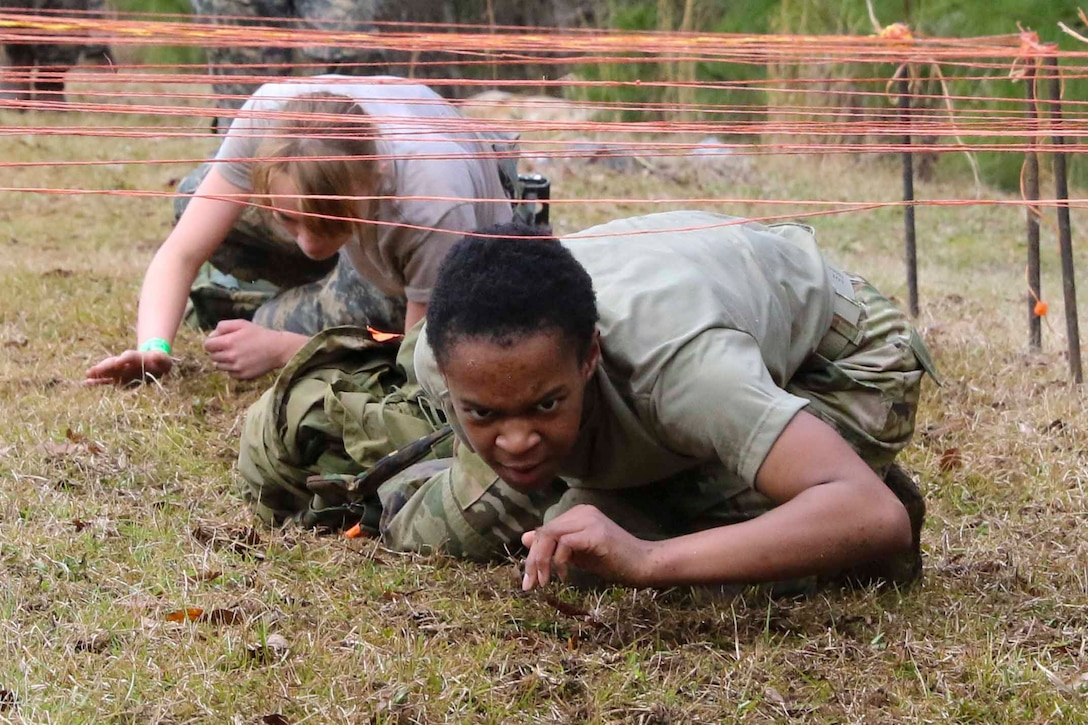 Two Army cadets crawl through an obstacle.